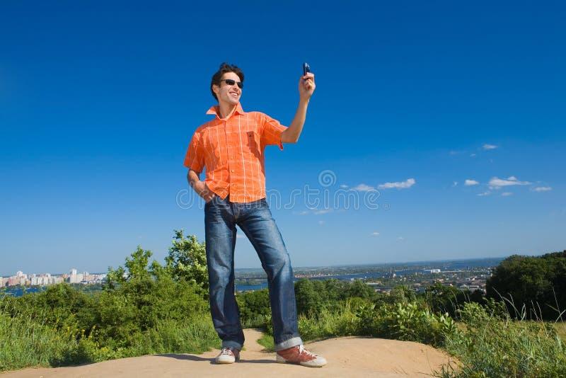 Stattlicher junger Mann, der eine Handyabbildung sendet lizenzfreie stockbilder