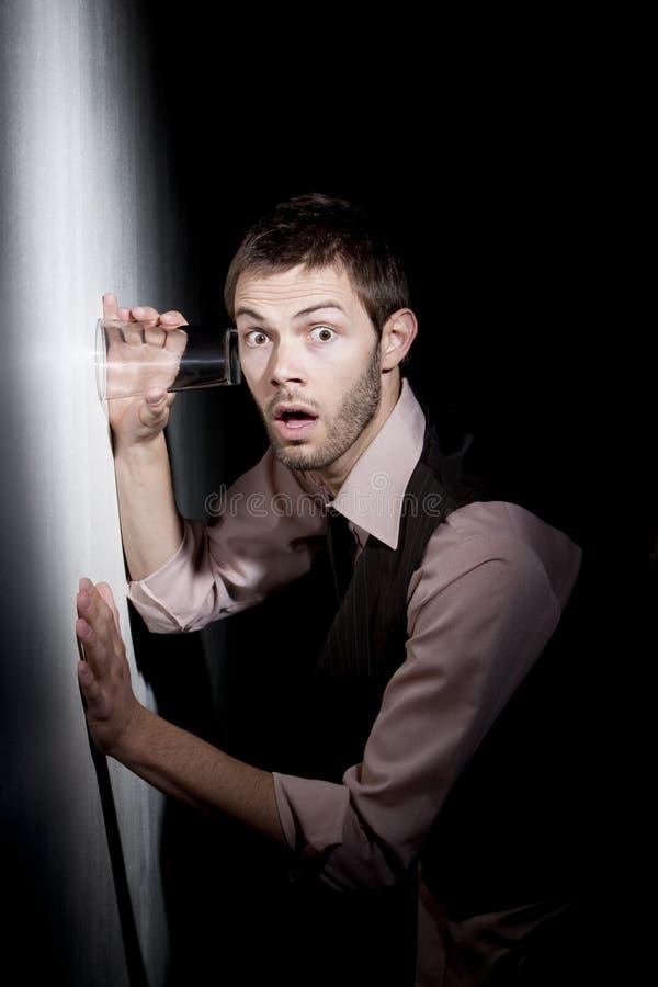 Stattlicher junger Mann, der Glas verwendet, um heimlich zuzuhören lizenzfreie stockfotografie