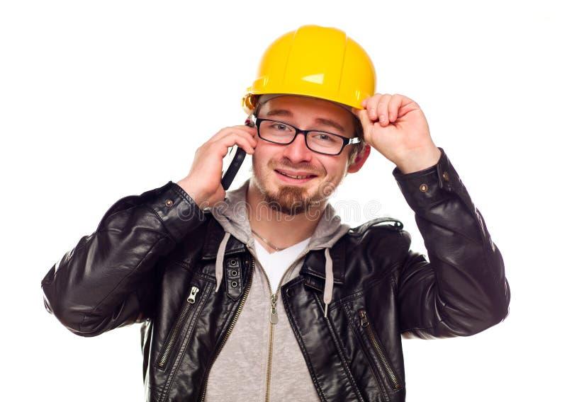 Stattlicher junger Mann im harten Hut am Telefon lizenzfreie stockfotos