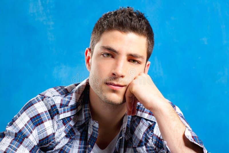 Stattlicher junger Mann mit Plaidhemd auf Blau lizenzfreie stockbilder