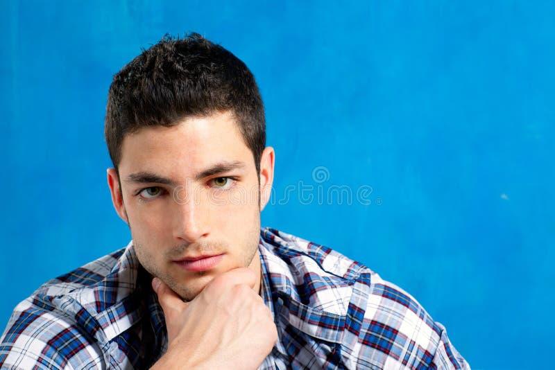 Stattlicher junger Mann mit Plaidhemd auf Blau stockfoto