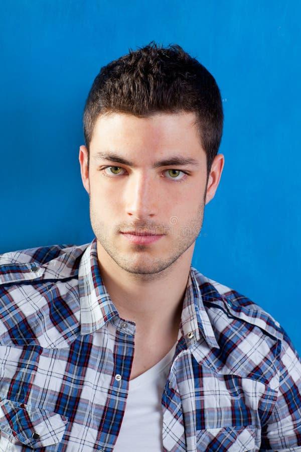 Stattlicher junger Mann mit Plaidhemd auf Blau lizenzfreies stockbild
