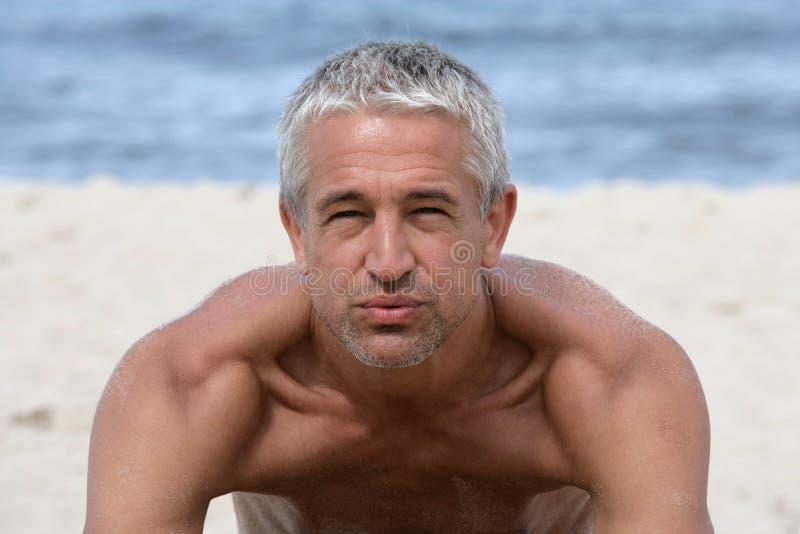 Stattlicher Mann auf dem Strand lizenzfreies stockbild