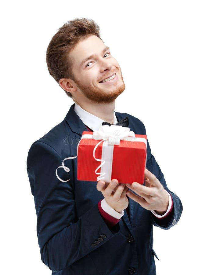 Stattlicher Mann bietet ein Geschenk an lizenzfreie stockbilder