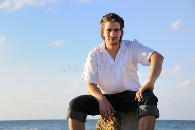 Stattlicher Mann, der durch das Meer sitzt stockbild