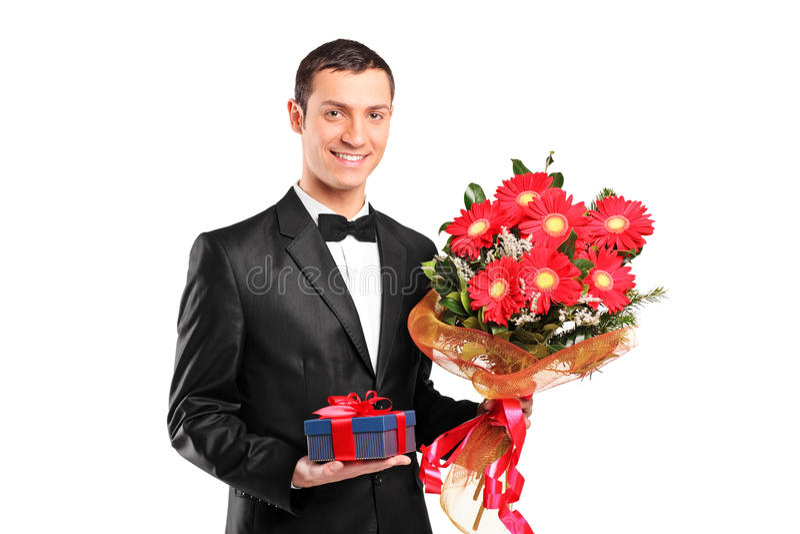 Stattlicher Mann, der einen Blumenstrauß der Blumen anhält stockbild