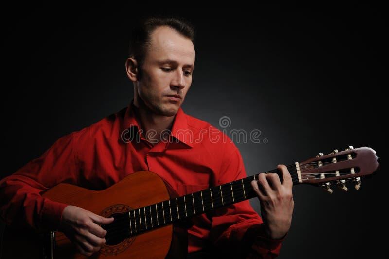 Stattlicher Mann, der Gitarre spielt lizenzfreies stockfoto