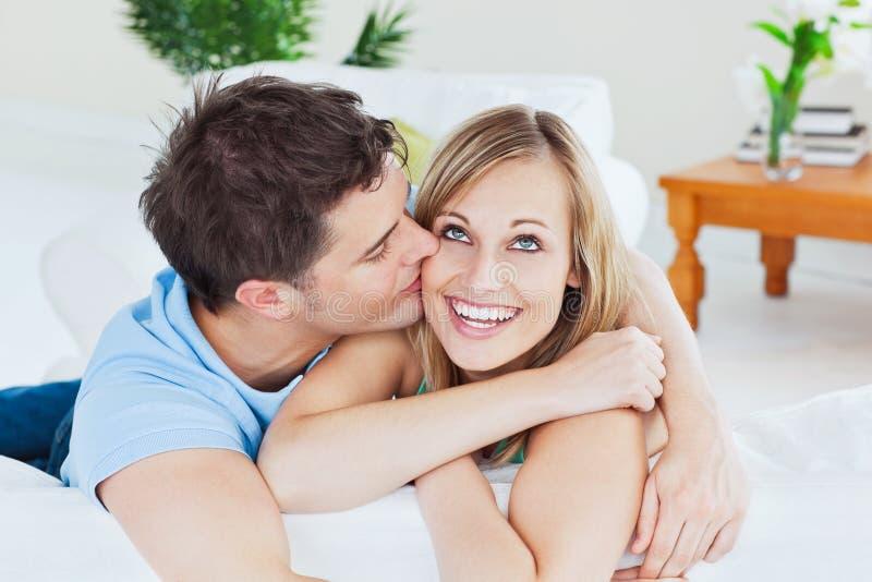 Stattlicher Mann, der seine frohe Freundin küßt lizenzfreies stockfoto