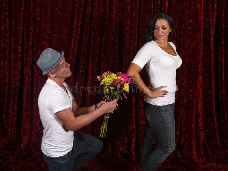 Stattlicher Mann knit mit Blumen für Freundin lizenzfreies stockbild