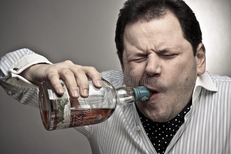 Stattlicher Mann mit einer Flasche des Kognaks. lizenzfreie stockbilder