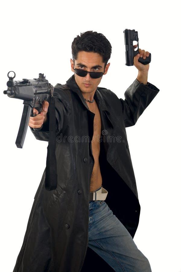 Stattlicher Mann mit Gewehr im ledernen Regenmantel lizenzfreie stockbilder