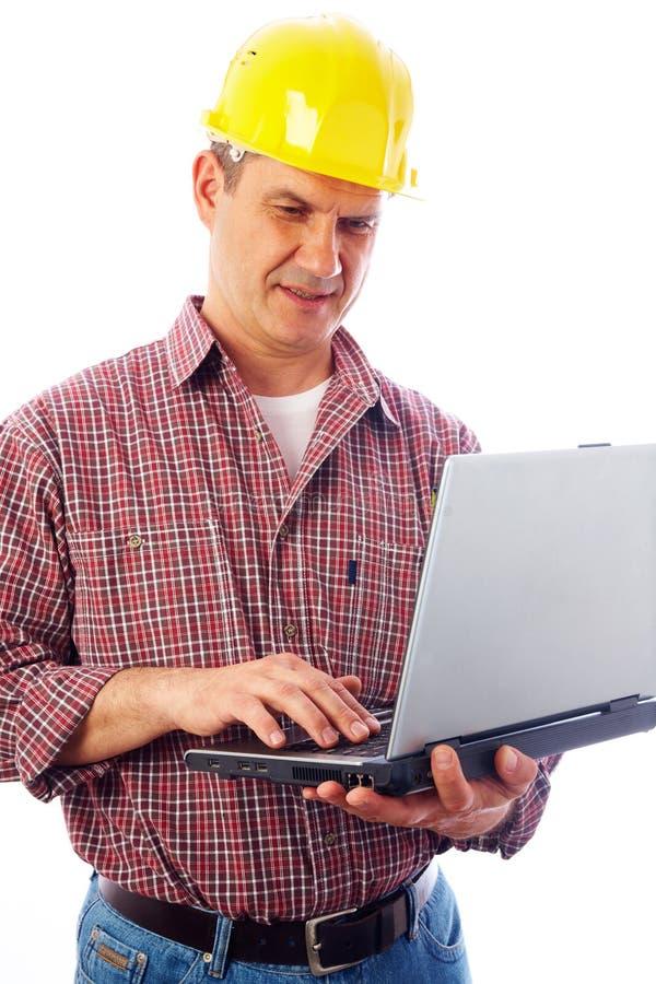 Stattlicher Mannerbauer mit Laptop stockbilder