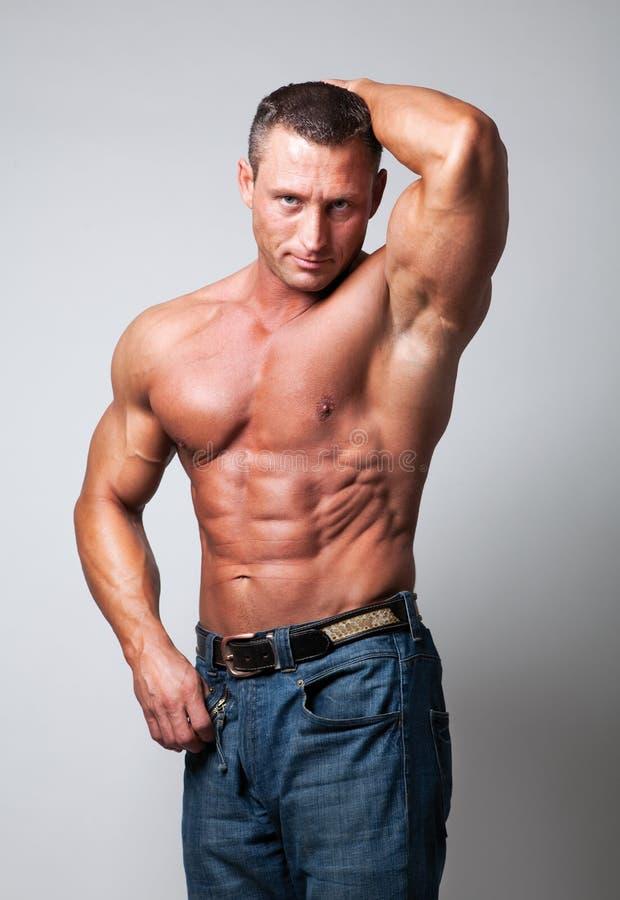 Stattlicher mit nacktem Oberkörper Mann - grauer Hintergrund stockbilder