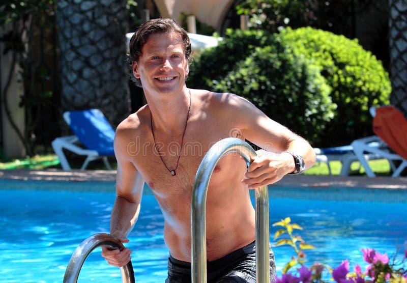 Stattlicher mittlerer gealterter Mann, der aus Swimmingpool heraus steigt stockbilder