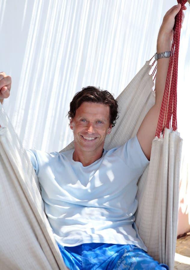 Stattlicher mittlerer gealterter Mann, der in der Hängematte sitzt stockbild