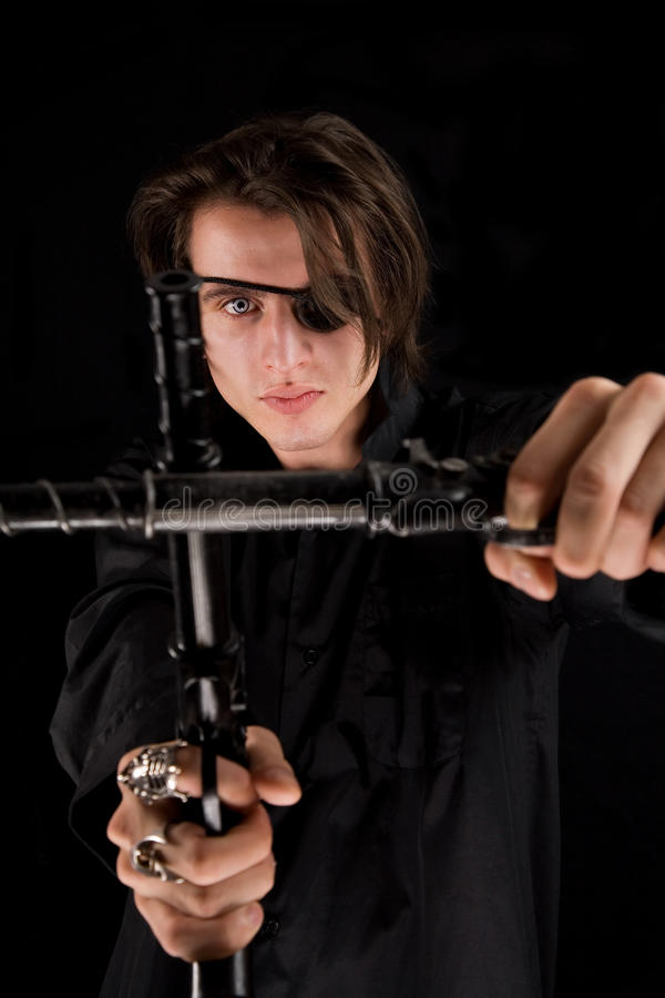 Stattlicher Pirat mit der Augeänderung am Objektprogramm, welche die Gewehren kreuzt stockfotos