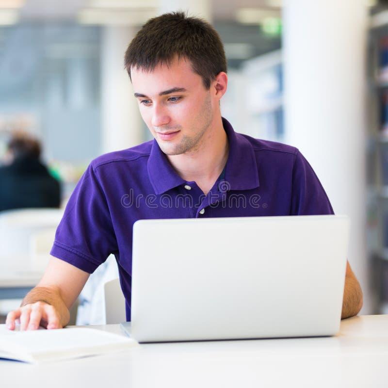 Stattlicher Student, der seinen Laptop verwendet stockbild