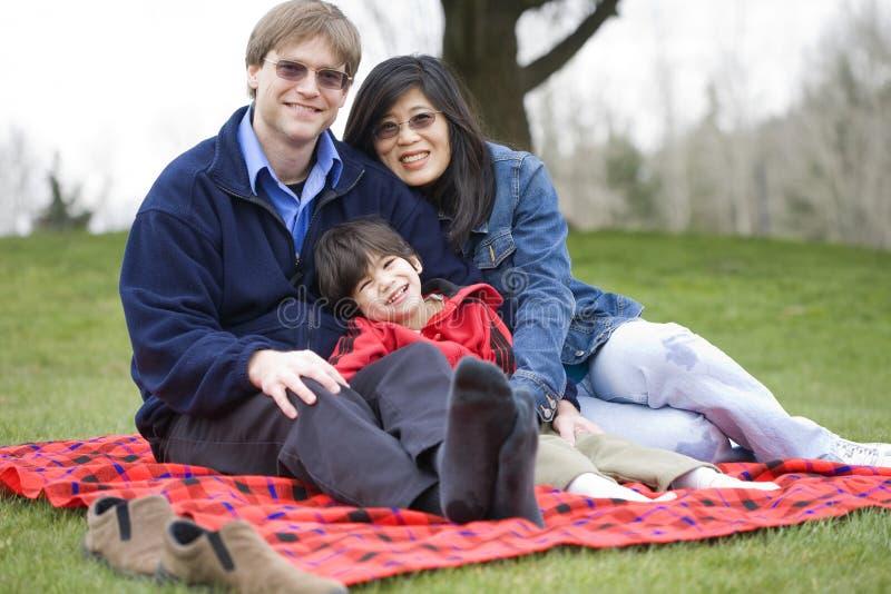 Stattlicher Vater, der am Park mit untauglichem Sohn sitzt lizenzfreie stockfotografie