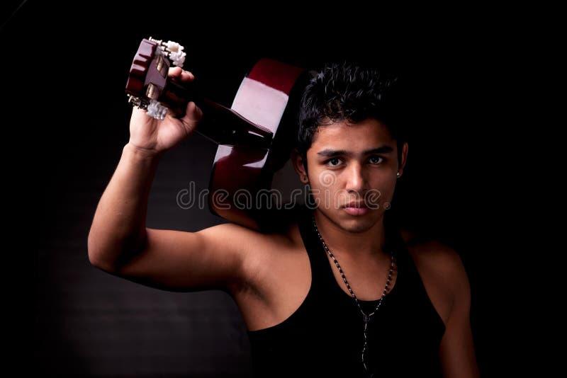 Stattliches reizvolles junges lateinisches Mannmusiker-Gitarrenspiel stockfotografie