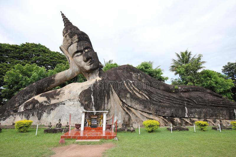Statua adagiantesi di Buddha nel parco di Wat Xieng Khuan Buddha immagine stock libera da diritti