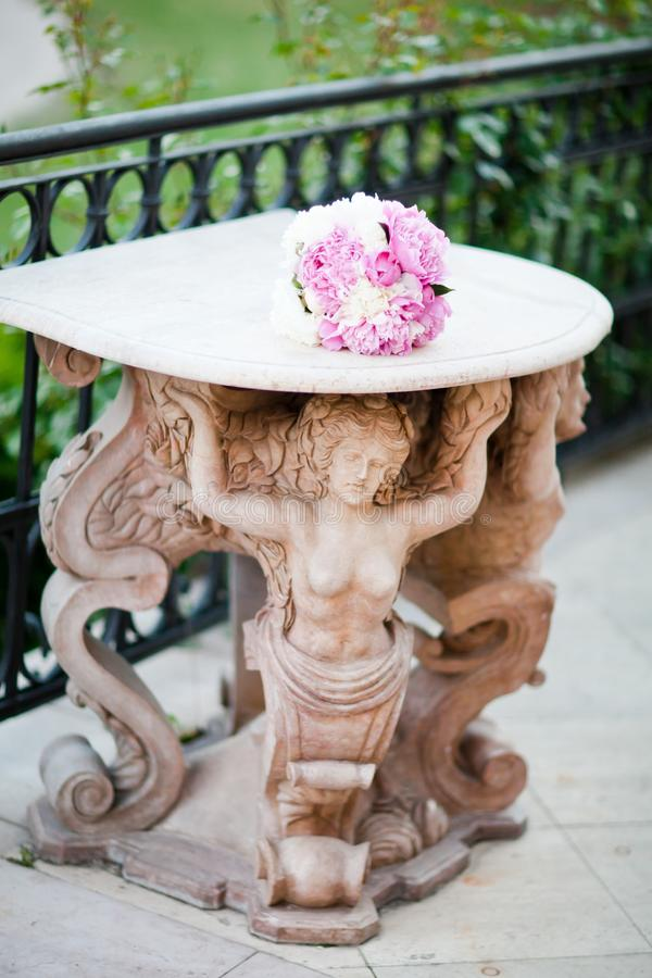 Statua antica che sostiene una tavola con il mazzo di nozze fotografia stock libera da diritti