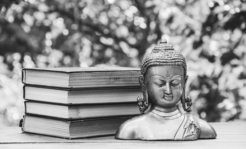 Statua antica di Buddha e una pila di libri Religione e cultura fotografia stock