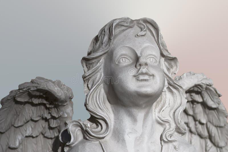 Statua biały kamienny modlenie anioł na pastelowym backgrouond, twarzy i skrzydłach, obraz royalty free