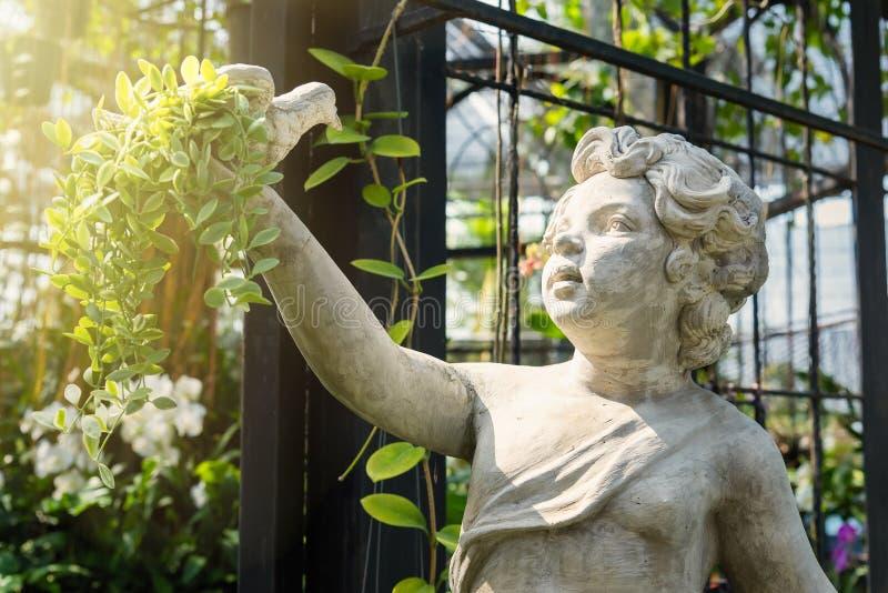 Statua bianca del cupido che tiene un uccello sulla mano a garde verde immagini stock libere da diritti