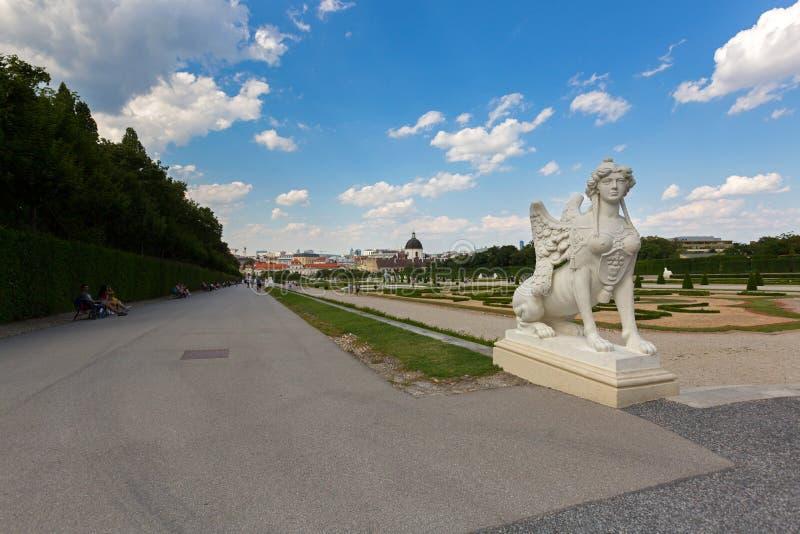 Statua bianca della Sfinge in giardino con gli ospiti che si siedono camminata seguente vicino al palazzo di belvedere a Vienna,  immagine stock libera da diritti