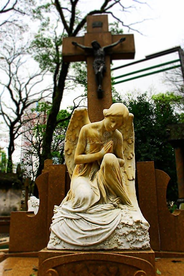 Statua bianca di angelo che si inginocchia sulla tomba fotografia stock
