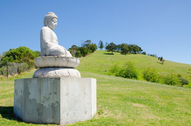 Statua bianca di Buddha che si siede sul campo verde con il Mountain View ed il giorno del cielo blu fotografia stock