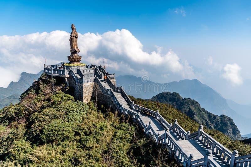 Statua Bodhisattva na Fansipan halnym szczycie wysoka g?ra w Indochina t?a Pi?knego widoku chmurze i niebieskim niebie zdjęcie stock