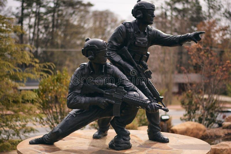 Statua che visualizza due giovani coraggiosi nei militari fotografie stock