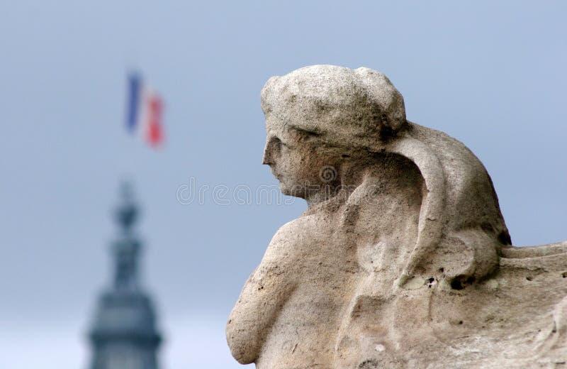 Statua con il volo della bandiera del francese fotografie stock libere da diritti