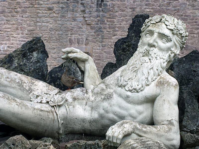 Statua con una brocca sopra il lago nel giardino della città fotografia stock