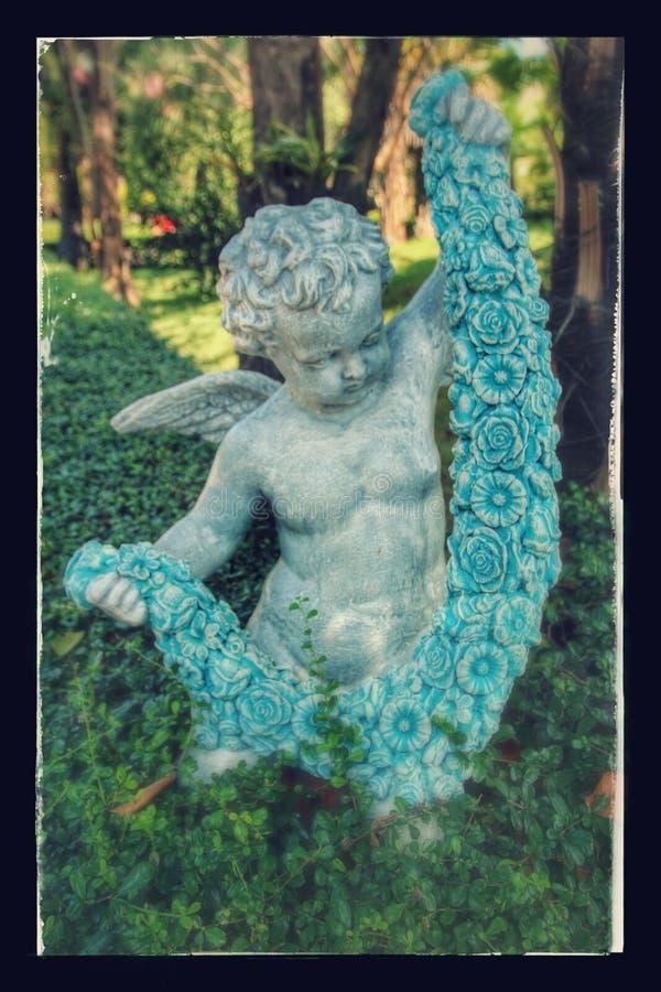 Statua del bambino nel giardino immagini stock