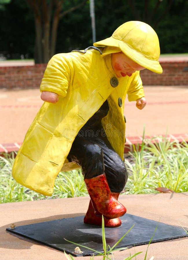 Statua del bambino piccolo che spruzza e che batte i piedi nella pioggia fotografia stock