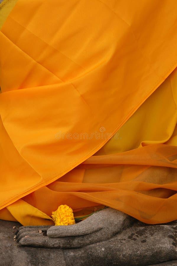 Statua del Buddha spostata in tessuto arancione immagine stock