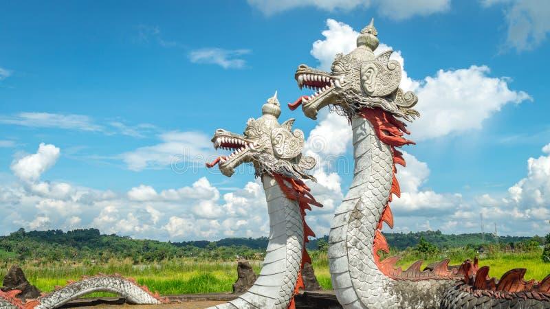 Statua del drago gemellato con il bello cielo come i precedenti in Pulau Kumala, Indonesia fotografia stock