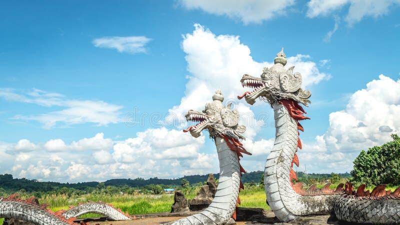 Statua del drago gemellato con il bello cielo come i precedenti in Pulau Kumala, Indonesia fotografia stock libera da diritti
