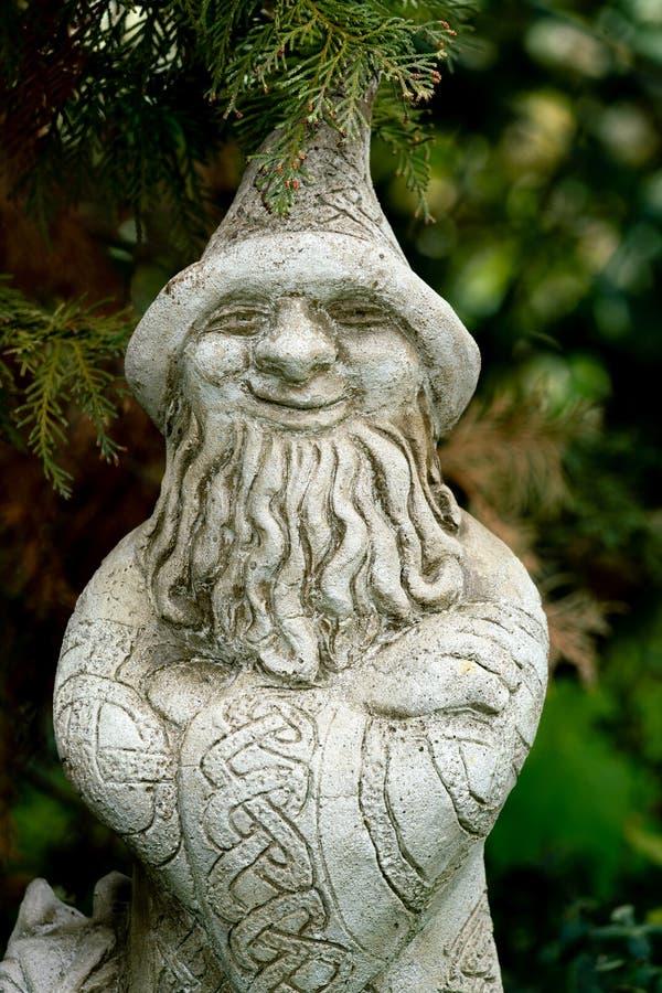 Statua del giardino di un mago con il cappello appuntito fotografia stock libera da diritti