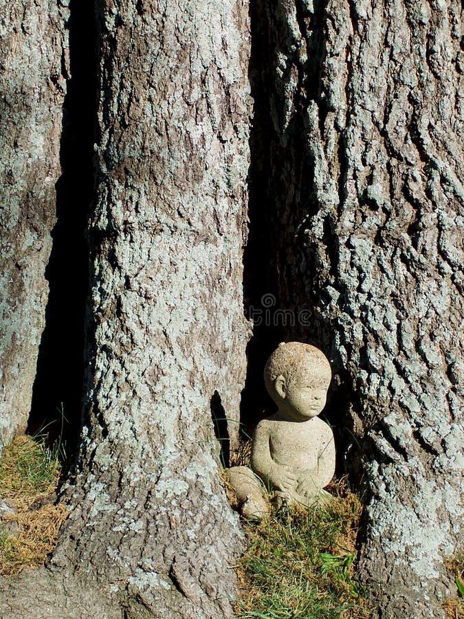 Statua del ragazzino al lato dell'albero fotografia stock libera da diritti