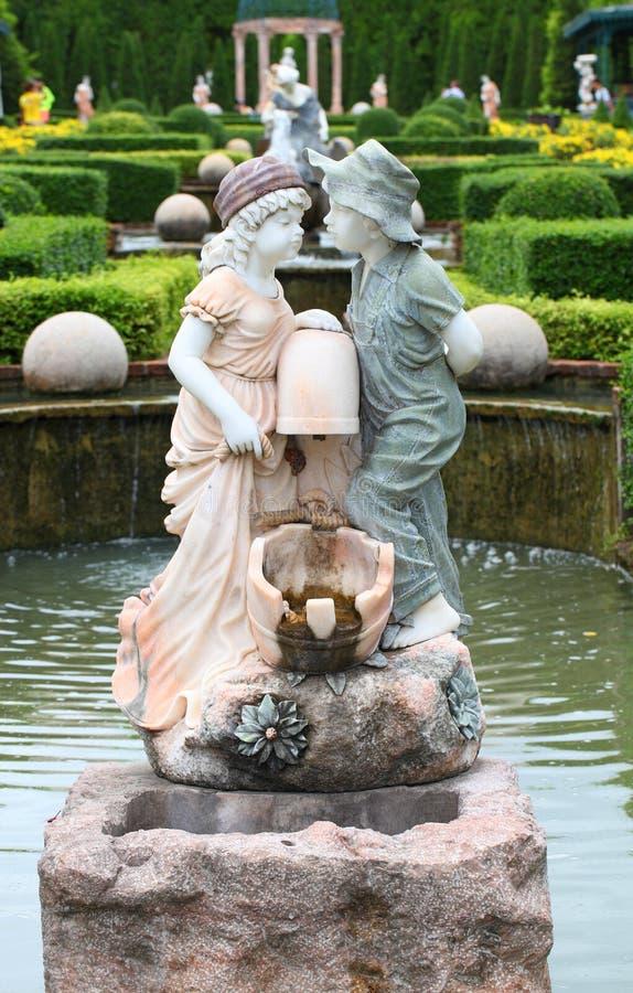 Statua del ragazzo e della ragazza belli nel giardino pubblico fotografia stock