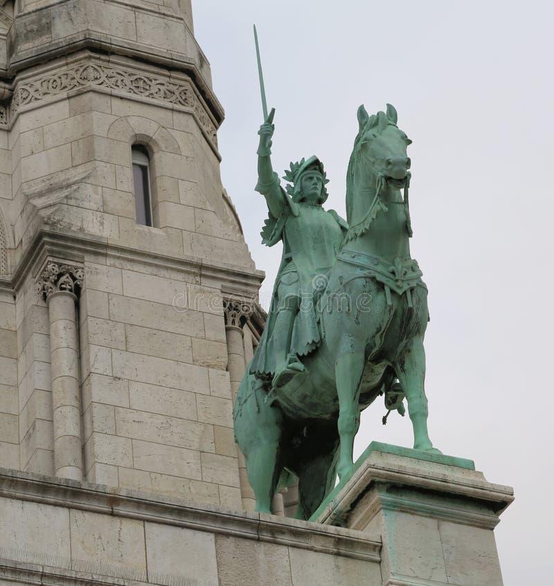 Statua del san Giovanna d'Arco e la basilica di cuore sacro dentro fotografia stock libera da diritti