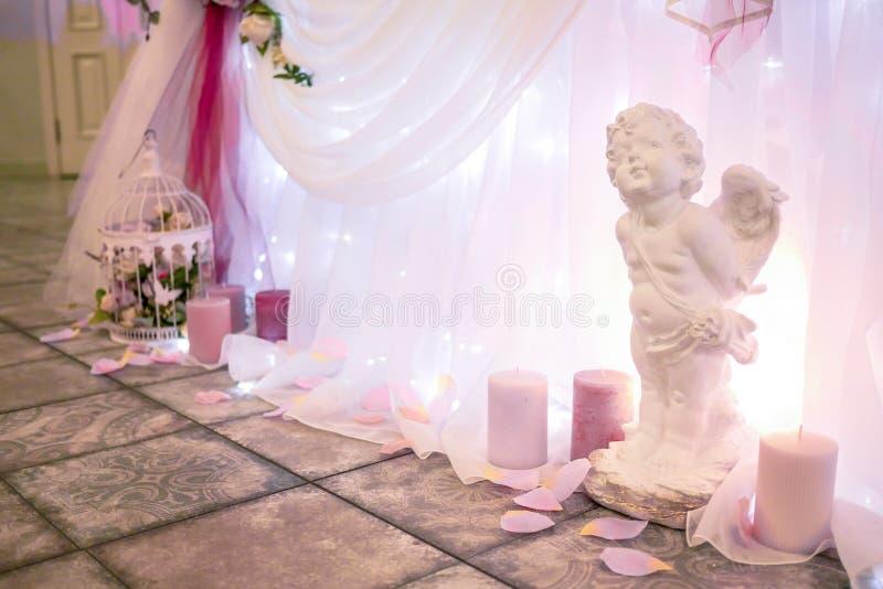Statua dell'angelo bianco di nozze con le candele fotografia stock libera da diritti