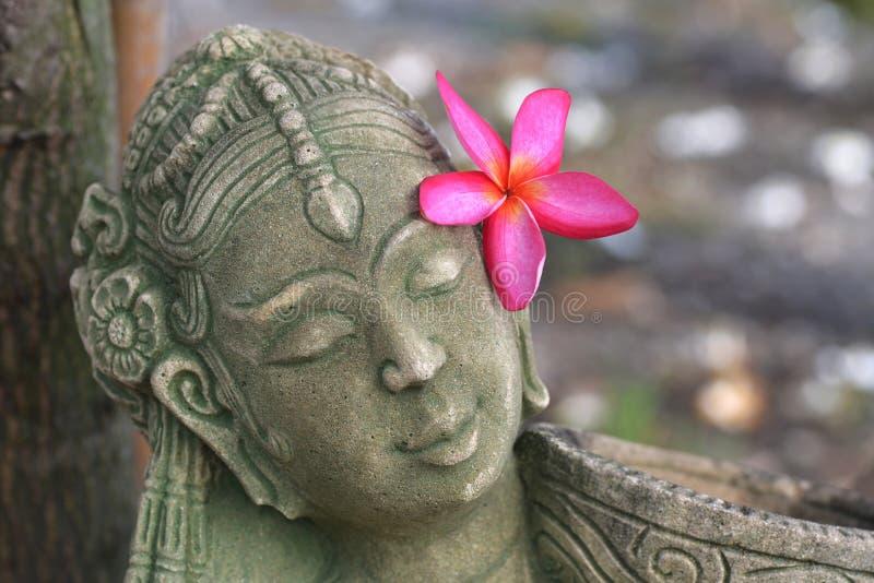 Statua della donna con il fiore rosso in suoi capelli fotografia stock libera da diritti