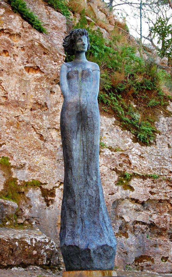 Statua della donna nel villaggio di Eze vicino alla costruzione di chiesa immagini stock