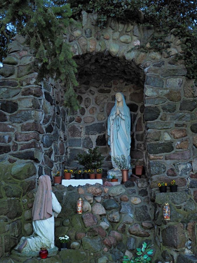 Statua della nostre signora e st Bernadette in grotta immagine stock libera da diritti