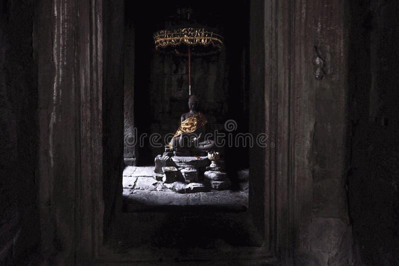Statua di Buddha avvolta in oro, ancora calmo dal passaggio della luce di mattina attraverso la finestra del tempio di Bayon a An immagine stock
