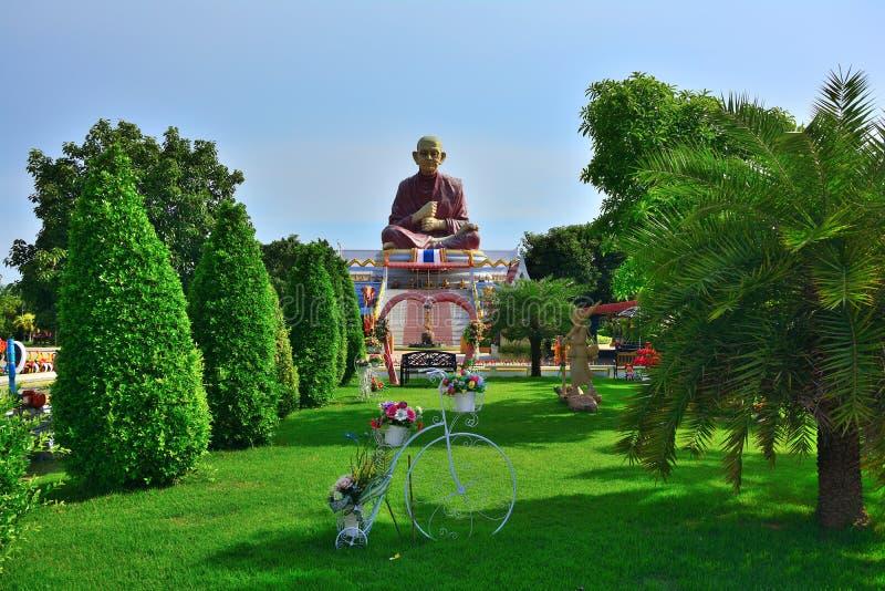 Statua di Buddha che si siede sul giardino verde in Tailandia immagini stock